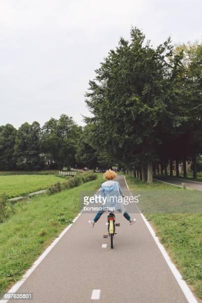 rear view of girl riding bicycle on street at park - bortes stock-fotos und bilder