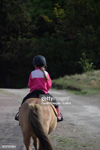 Rear View Of Girl Riding Horse On Road