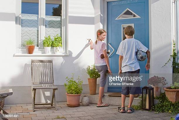 Rear view of girl ringing doorbell and looking at boy standing beside her