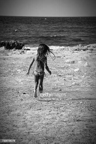 rear view of girl running at beach against sky on sunny day - bikini bottom stock pictures, royalty-free photos & images