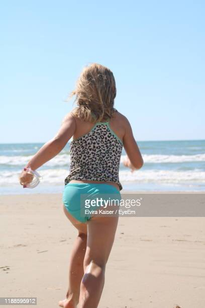 rear view of girl running beach against sky - petite fille culotte photos et images de collection