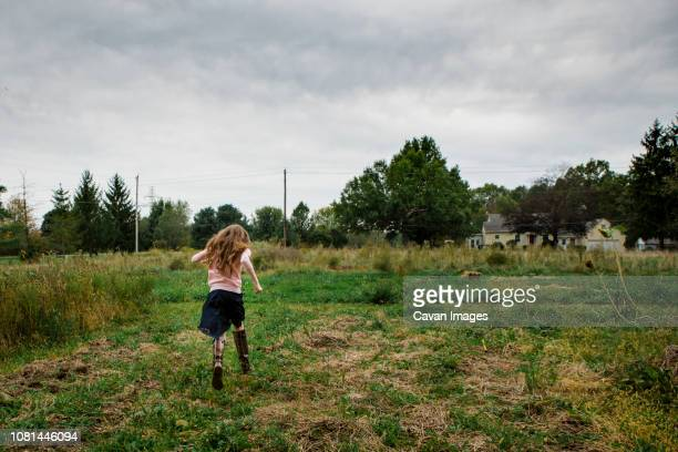 Rear view of girl running on grassy field against cloudy sky