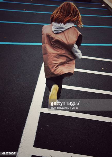 rear view of girl running on zebra crossing - zebra crossing stock photos and pictures