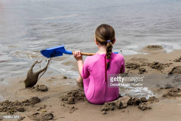 Rear View Of Girl Sitting On Beach
