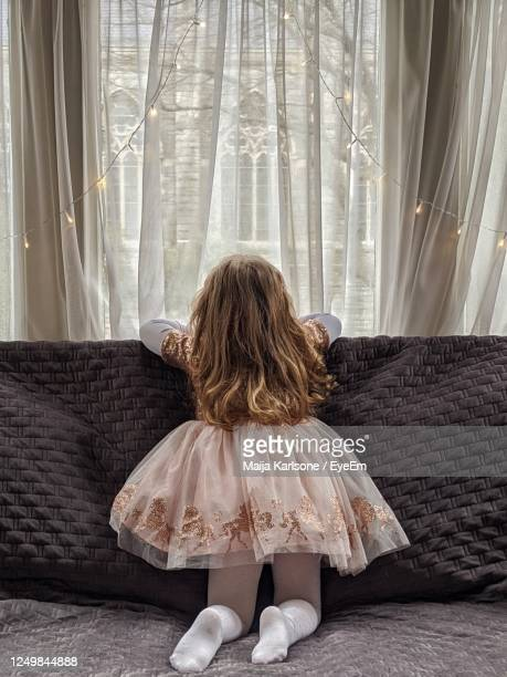rear view of girl sitting on sofa at home, looking out the window - back stock pictures, royalty-free photos & images