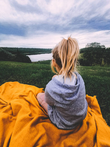 Rear View Of Girl Sitting On Yellow Blanket Against Sky