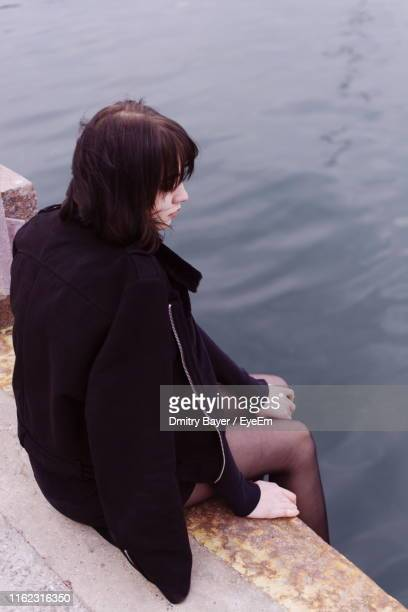 Rear View Of Girl Sitting Over Sea