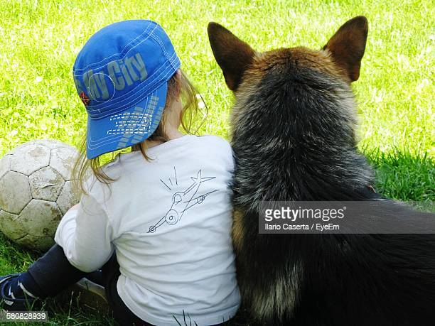 Rear View Of Girl Sitting With Dog At Park