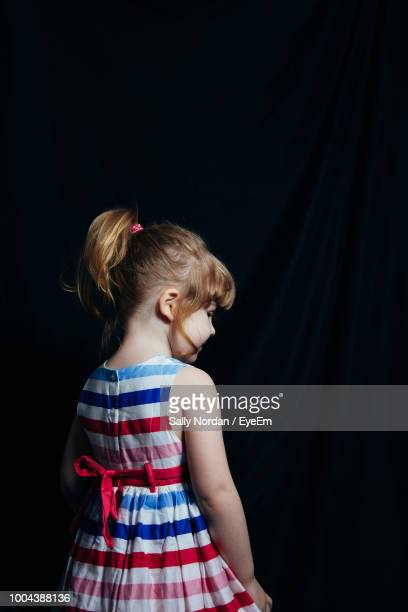 Rear View Of Girl Standing Against Black Backdrop