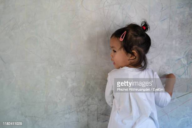 rear view of girl standing against wall - phichet ritthiruangdet stock photos and pictures