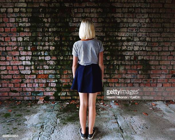 Rear View Of Girl Standing Against Weathered Brick Wall In Abandoned House