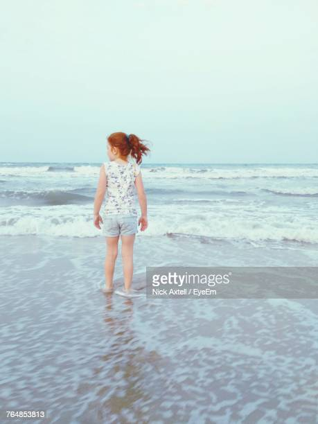 Rear View Of Girl Standing At Beach Against Clear Sky