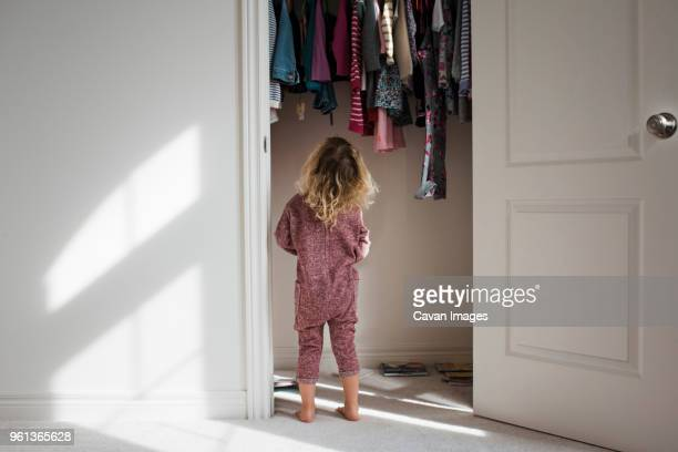 rear view of girl standing at closet - closet stock pictures, royalty-free photos & images
