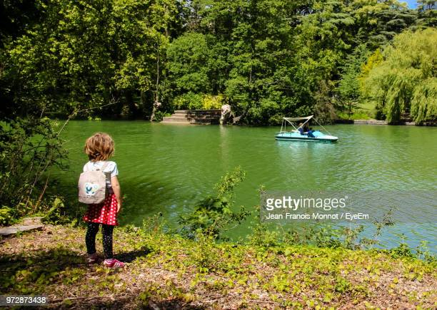 rear view of girl standing by lake at park - auvergne rhône alpes stock pictures, royalty-free photos & images