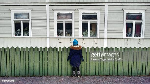 Rear View Of Girl Standing By Picket Fence Looking At House