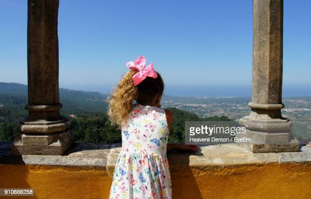 Rear View Of Girl Standing By Retaining Wall Against Clear Sky