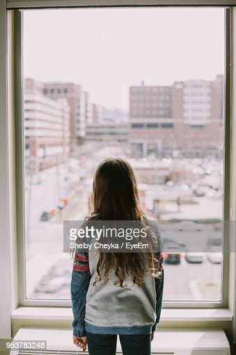 Rear View Of Girl Standing In Front Of Apartment Window