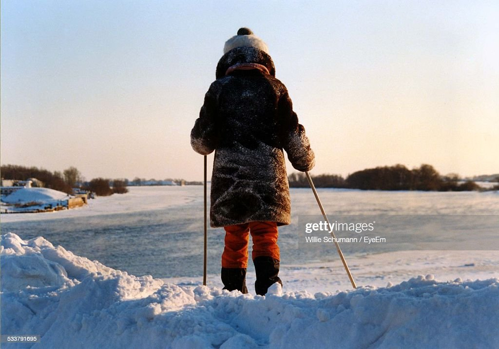 Rear View Of Girl Standing In Snow Holding Ski Poles : Foto stock