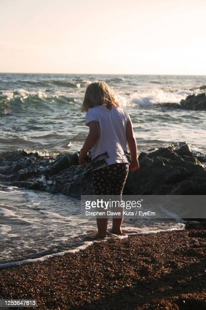 rear view of girl standing on beach - newquay stock pictures, royalty-free photos & images