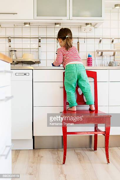 Rear view of girl standing on chair while working in kitchen