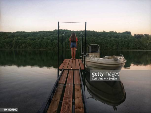rear view of girl standing on pier over lake at sunset - cyril montana photos et images de collection