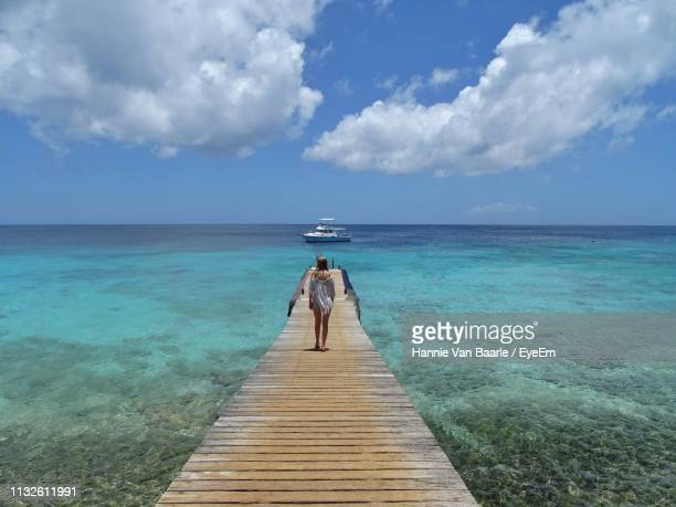 Rear View Of Girl Standing On Pier Over Sea Against Sky