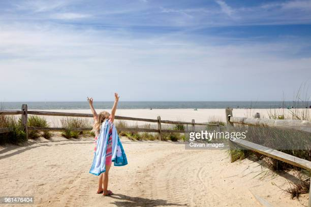 rear view of girl standing with arms raised at beach against sky - cape may stock pictures, royalty-free photos & images