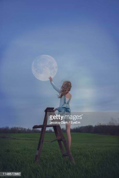 rear view of girl touching moon while standing on ladder - ladder to the moon stock pictures, royalty-free photos & images