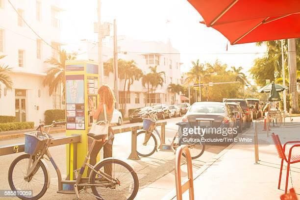 Rear view of girl using self service machine at bike rental stand, South Beach, Miami, Florida, USA
