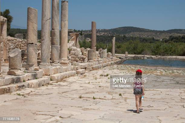 rear view of girl walking by old ruins - ancient civilization stock photos and pictures