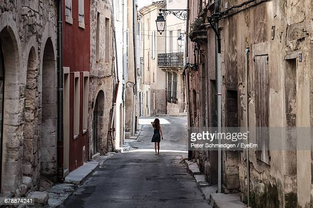 Rear View Of Girl Walking On Alley Amidst Old Buildings In Town
