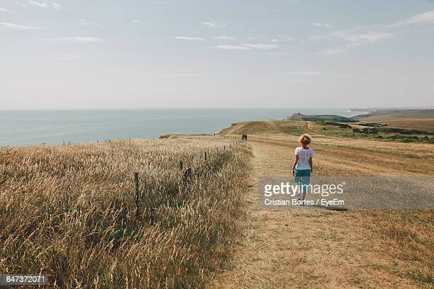 rear view of girl walking on field by sea against sky - bottomless girls stock photos and pictures