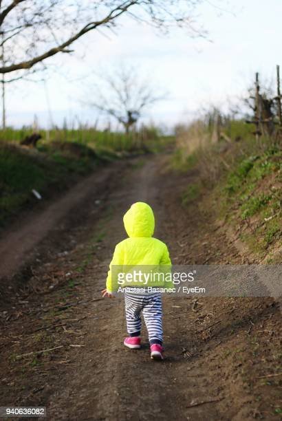 rear view of girl walking on footpath - anastasi foto e immagini stock