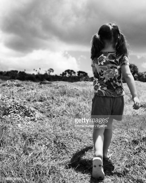 rear view of girl walking on grassy land against sky - emma hunter eye em stock photos and pictures