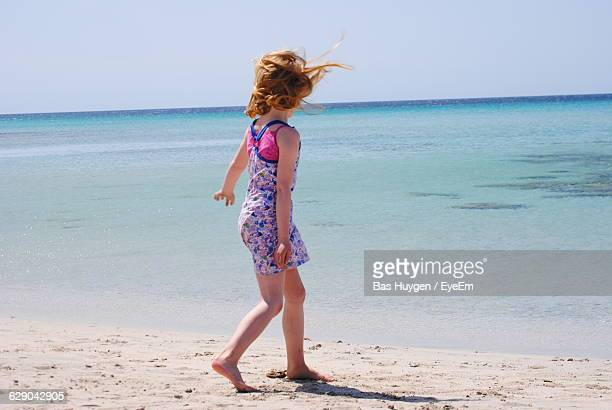Rear View Of Girl Walking On Shore Against Sea And Sky
