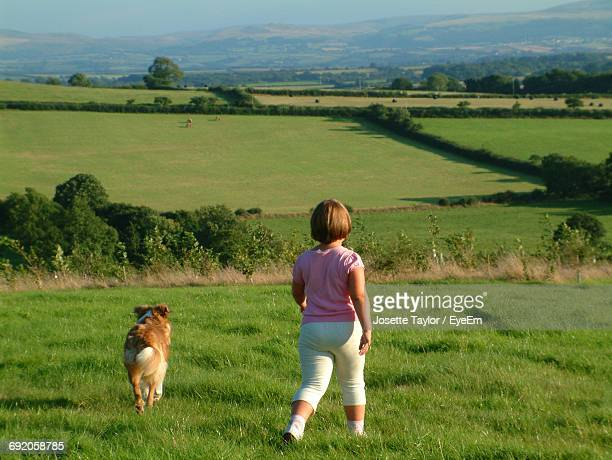 Rear View Of Girl Walking With Dog On Grassy Field At Winkleigh