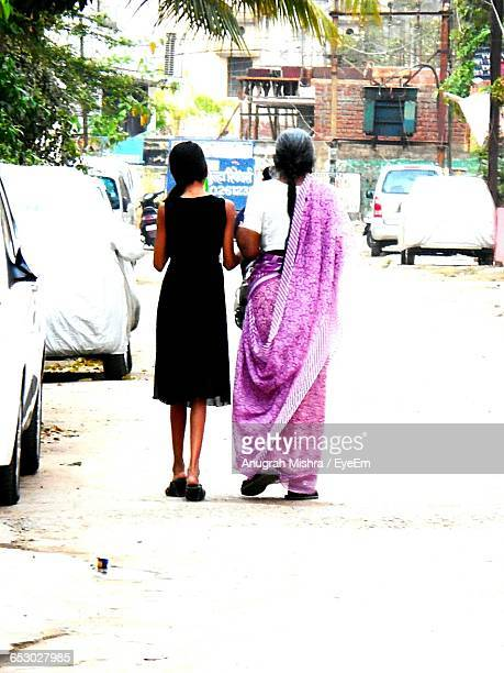 Rear View Of Girl Walking With Granddaughter On Street