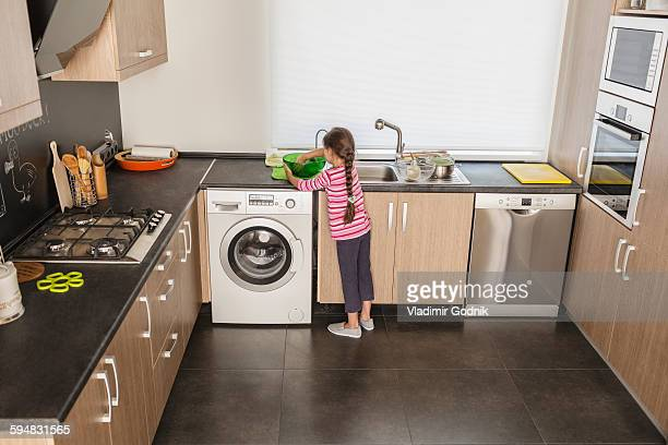Rear view of girl washing dishes in kitchen