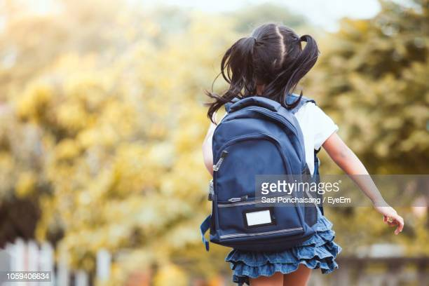 rear view of girl wearing backpack while walking against trees - riapertura delle scuole foto e immagini stock