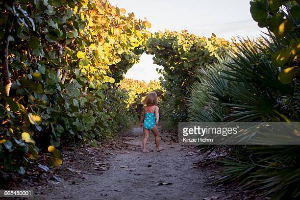rear view of girl wearing bathing costume exploring park, blowing rocks preserve, jupiter island, florida, usa - jupiter island florida stock photos and pictures
