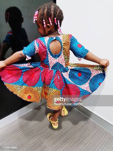 Rear View Of Girl Wearing Colorful Dress While Standing Against Wall