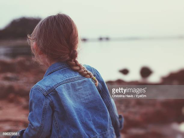 Rear View Of Girl Wearing Denim Jacket At Beach