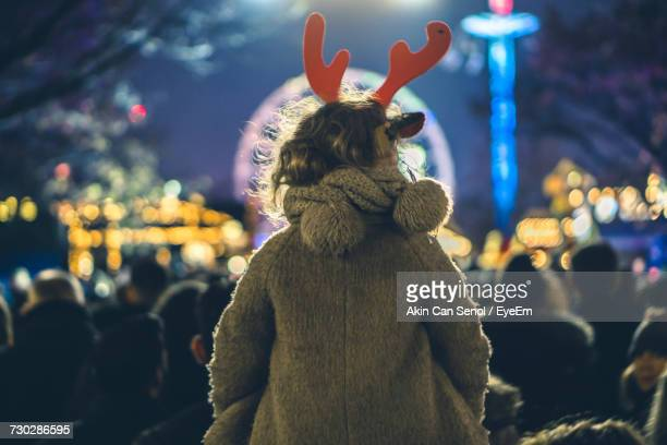 Rear View Of Girl Wearing Reindeer Headband With Crowd In Background At Hyde Park
