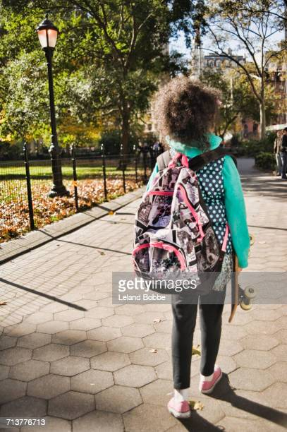 rear view of girl with backpack carrying skateboard, new york, usa - children only stock pictures, royalty-free photos & images