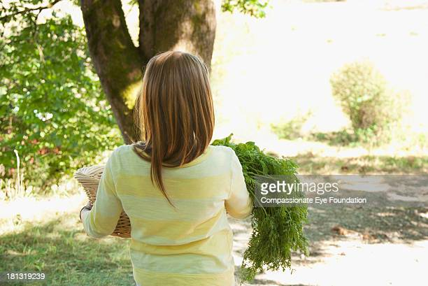 Rear view of girl with basket of vegetables