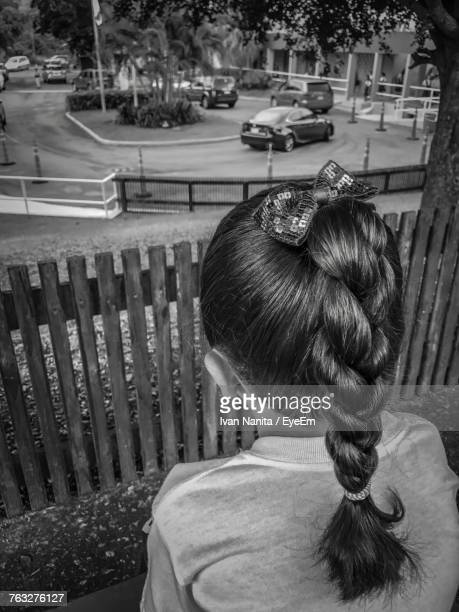 Rear View Of Girl With Braided Hair Looking At Cars On Road