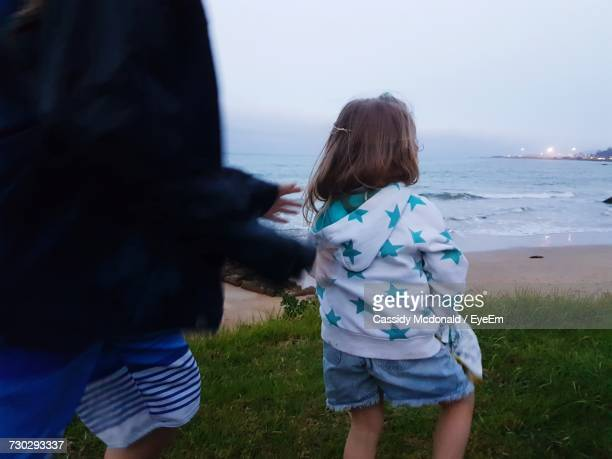 Rear View Of Girl With Brother Standing On Grassy Field At Beach Against Sky