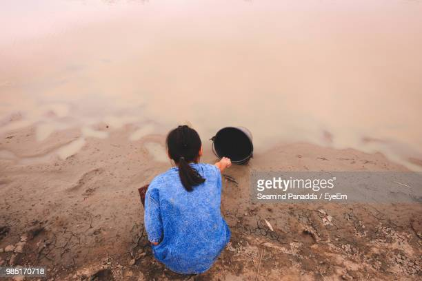 rear view of girl with bucket at lakeshore - natural disaster stock pictures, royalty-free photos & images