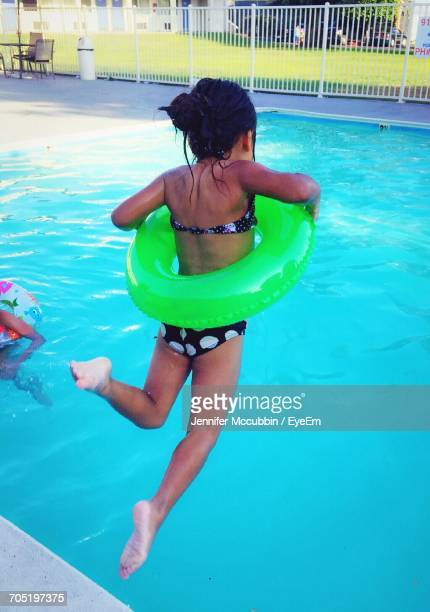 Rear View Of Girl With Inflatable Ring Jumping In Swimming Pool