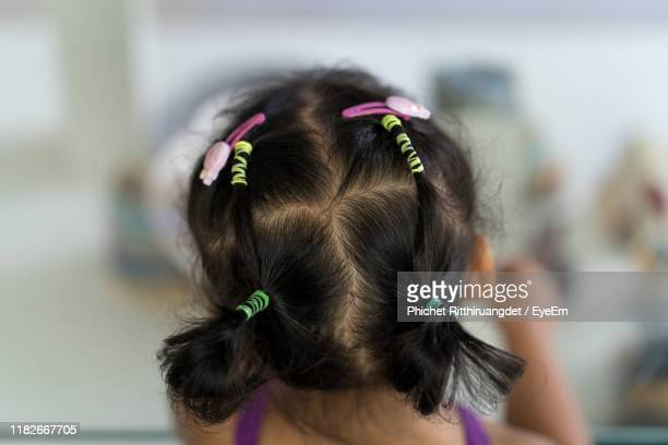 rear view of girl with pigtails - phichet ritthiruangdet stock photos and pictures